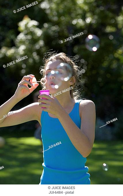Girl 11-13, in turquoise vest, standing in summer garden, blowing soap bubbles into air with bubble wand
