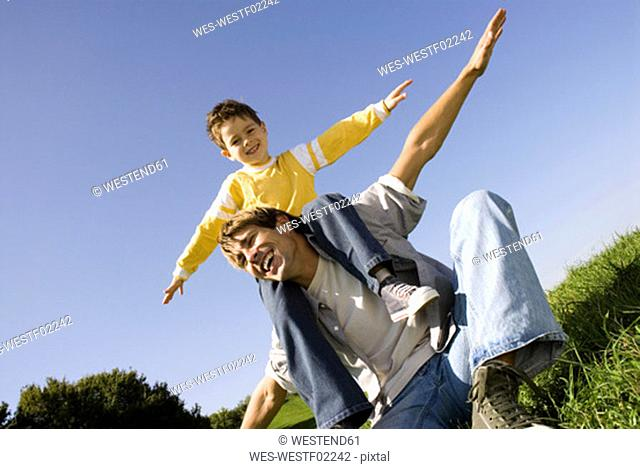 Boy (4-7) sitting on fathers shoulders, arms out