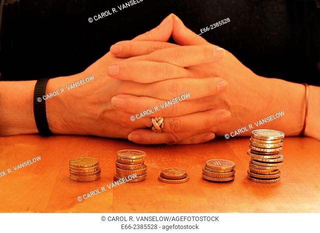 Woman with hands clasped. Stacks of euro coins in front of her on table
