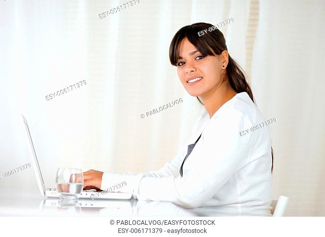 Portrait of a charming young woman looking at you while is working on laptop - copyspace