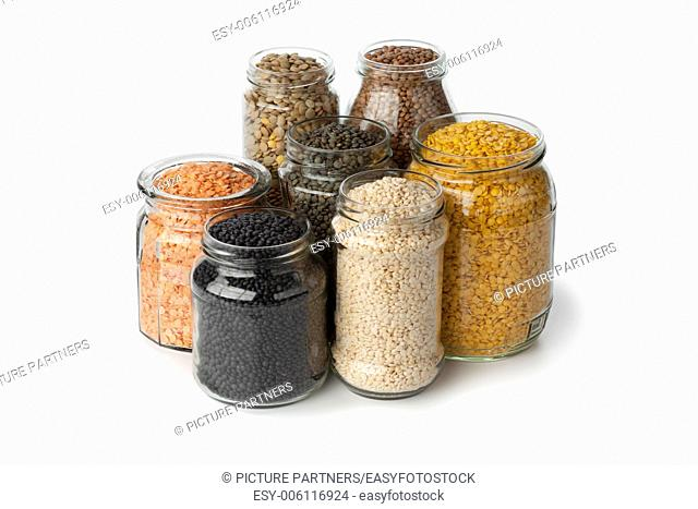 Variety of dried lentils in glass pots on white background