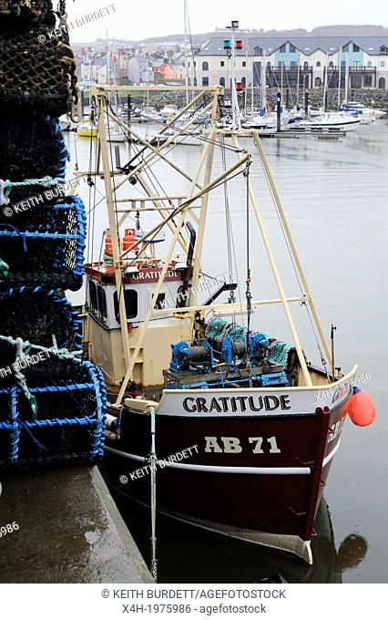Fishing boat at the quayside with stack of Lobster pots or creels, Aberystwyth, Wales, UK