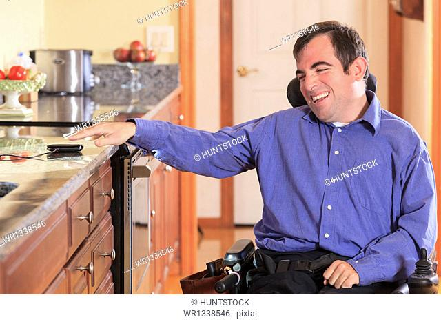 Man with Cerebral Palsy in his motorized wheelchair in his kitchen reaching for his cell phone