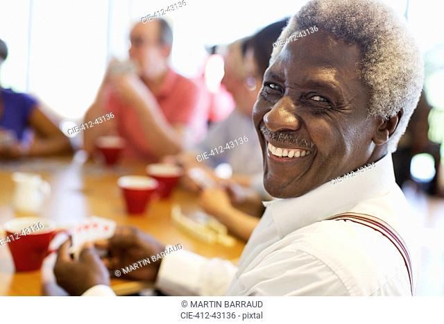 Portrait happy senior man playing cards with friends in community center