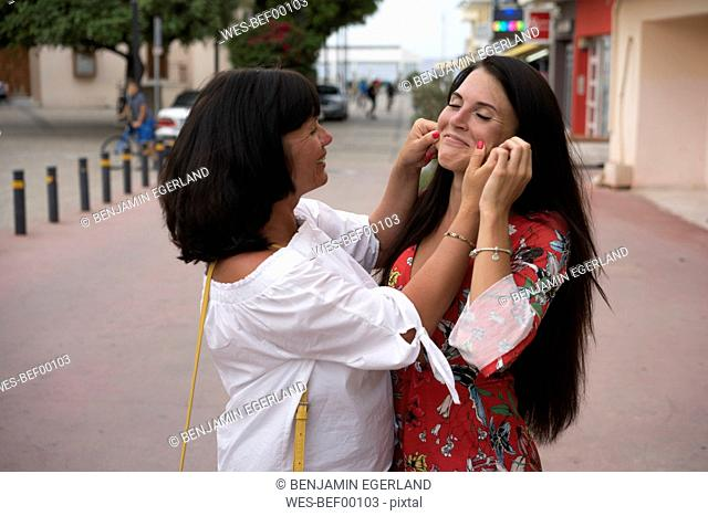 Greece, Crete, Limenas Chersonisou, mother and adult daughter having fun together