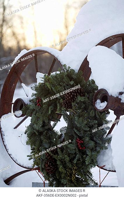 Holiday wreath hanging on snow covered farm equipment Mat-Su Valley Southcentral Alaska Winter