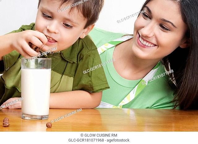 Boy adding cereal balls into a glass of milk