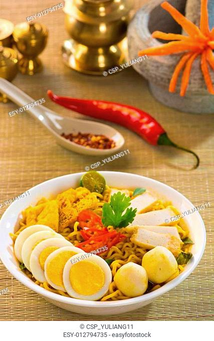 Spicy curry instant noodles. Asian cuisine, ready to serve on wooden dining table setting. Fresh hot with steamed smoke