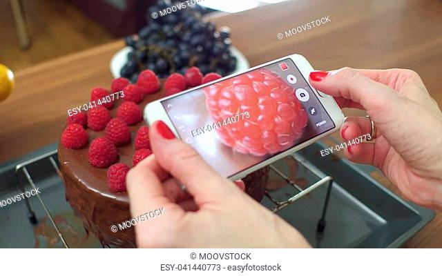 Young woman taking photos of her freshly cooked raspberry cake at home. Amateur cooking and social media concept