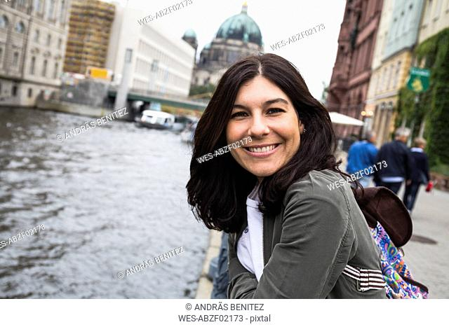 Germany, Berlin, portrait of smiling young woman in the city