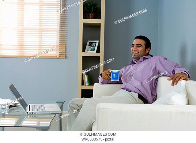 Man holding cup, sitting in the living room