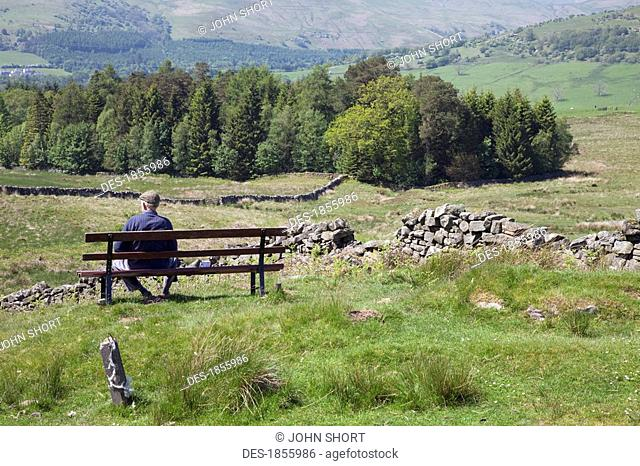 Man on bench in countryside, Dumfries and Galloway, Scotland