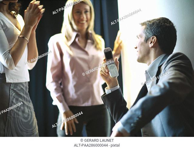 Businessman holding up cellphone, female colleagues smiling and clapping
