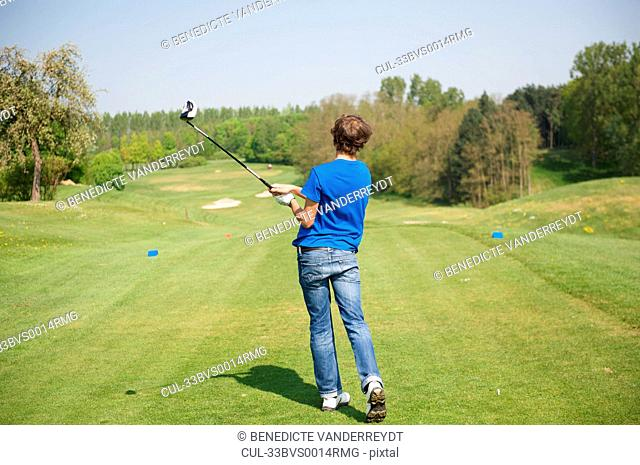 Boy swinging club on golf course