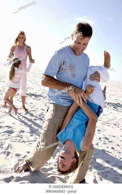 Mid adult couple playing with their children on the beach