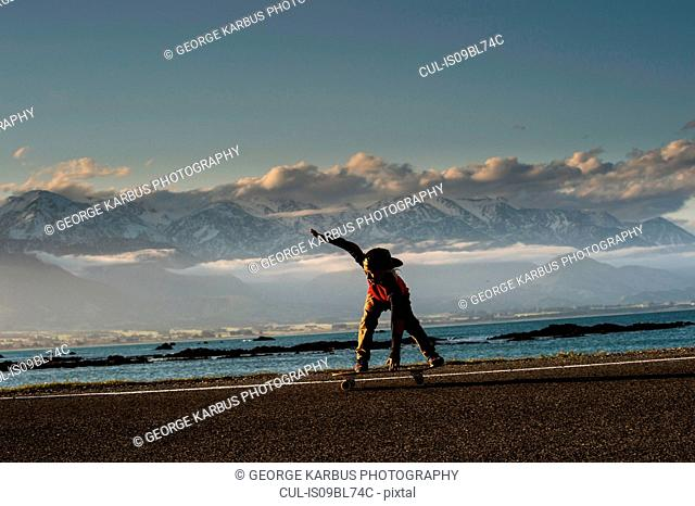 Young boy skateboarding along coastal road, Kaikoura, Gisborne, New Zealand