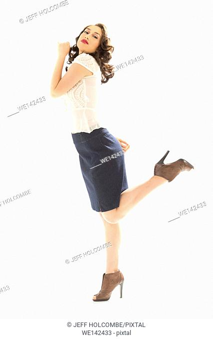 Beautiful young woman in white blouse and blue denim skirt, full length in brown heels, profile with one leg up and head back