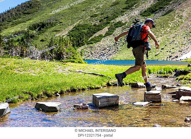 Male hiker leaping on rocks across a creek with alpine lake and mountain hillside in the background; Waterton, Alberta, Canada