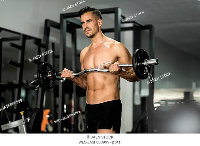 Man lifting barbell in gym