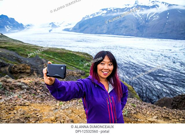 An asian female hiker takes a self-portrait from the mountain top with the glacier in the background at Vatnajokull National Park; Iceland