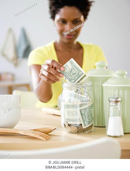 Black woman putting money in jar