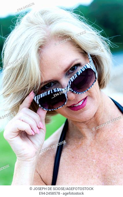 A portrait of a 56 year old blond woman looking over her sunglasses directly at the camera, outdoors
