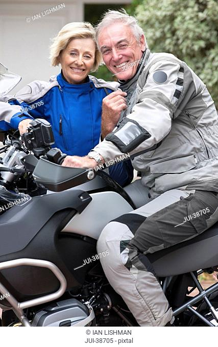 Portrait of smiling senior couple on motorcycle in driveway