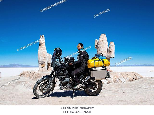 Woman sitting on touring motorbike, Salinas grandes close to Susques before the Paso de Jama border crossing, Susques, Jujuy, Argentina, South America