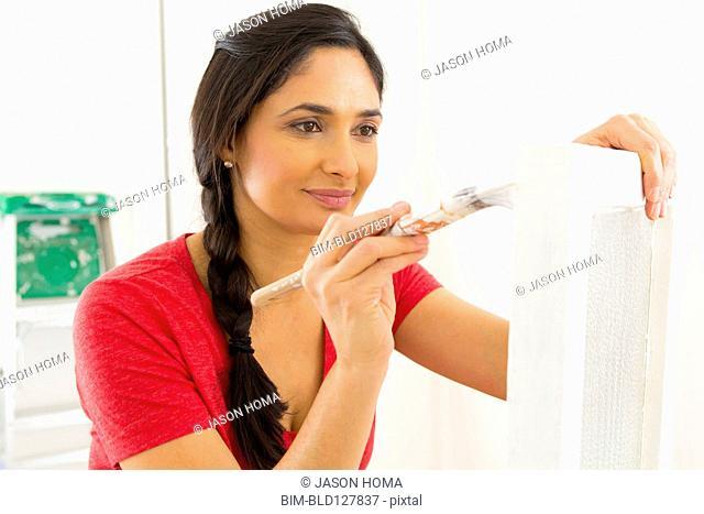 Mixed race woman painting window pane
