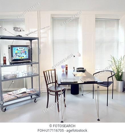 Television on movable metal shelf unit in seventies study dining room with grey flooring