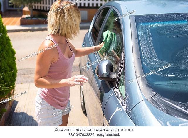 Young woman cleaning car with microfiber cloth. Car detailing