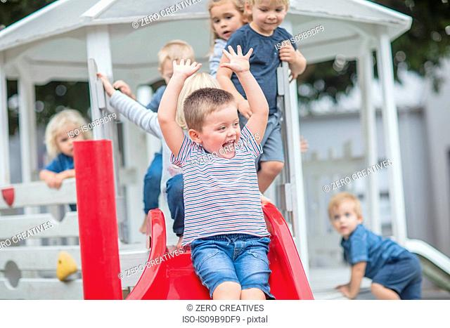 Boys and girls at preschool, sliding on playground slide in garden