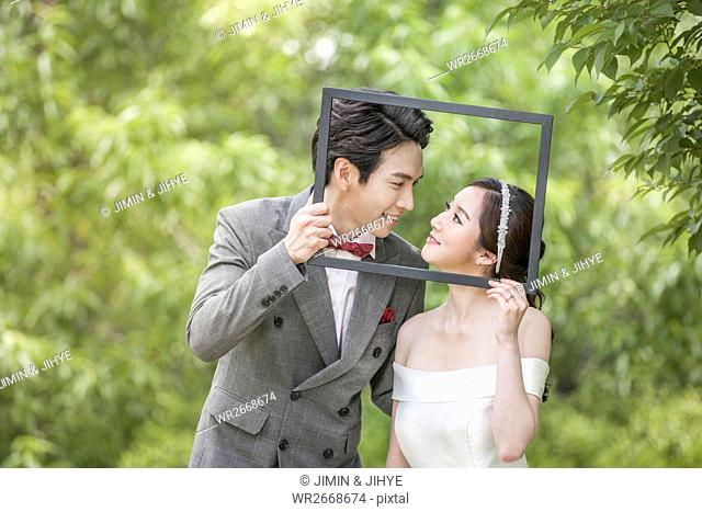 Portrait of young wedding couple with frame posing outdoors