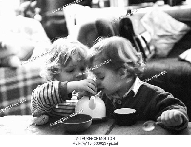Two children having tea party, b&w