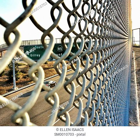 Looking through a chain link fence of a highway overpass to the signs and the road below, on Highway 85 in California