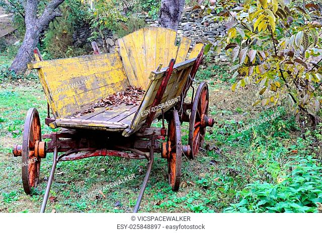 Old shabby wooden yellow cart in the garden