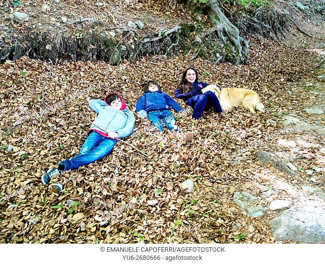 Siblings with their dog are lying in the leaves on the path of a forest