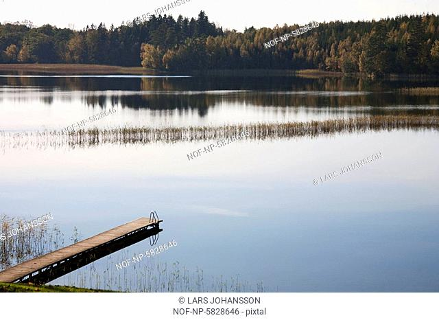 Wooden pier in the lake at autumn. Sweden