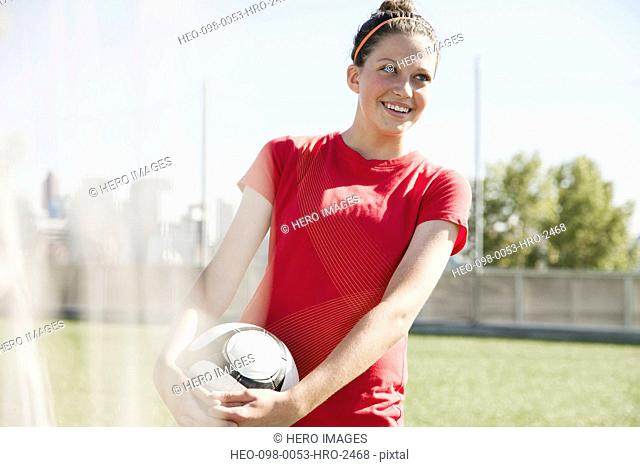 Teenage soccer player smiling while holding soccer ball