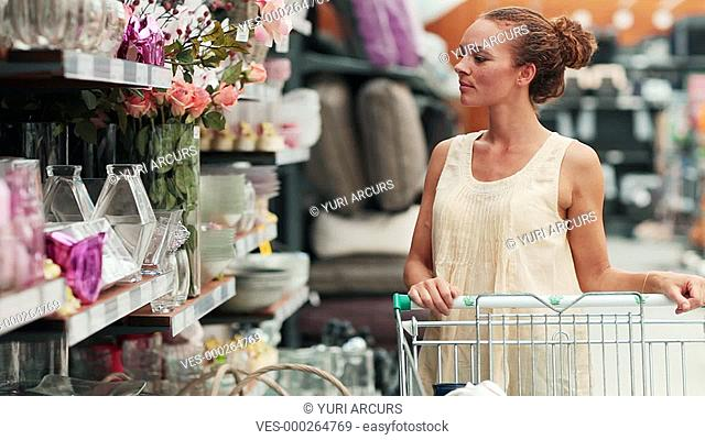Pretty young woman picking up and looking at an item in an interior decorating store