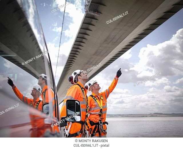 Bridge workers and support truck under suspension bridge. The Humber Bridge, UK was built in 1981 and at the time was the world's largest single-span suspension...