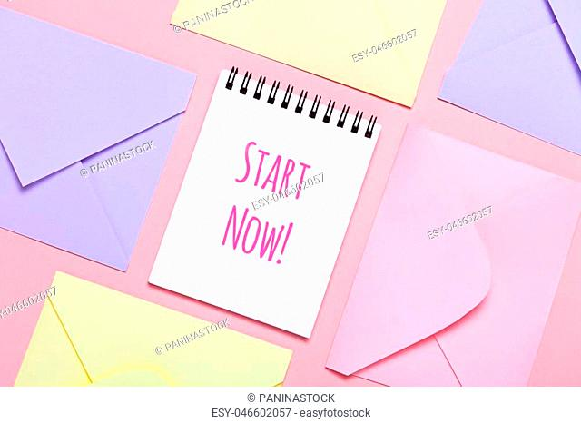 Frame from colorful envelopes and notepad on pink table top view. Worns Start Now. Mockup for business mail, blogging and office correspondence