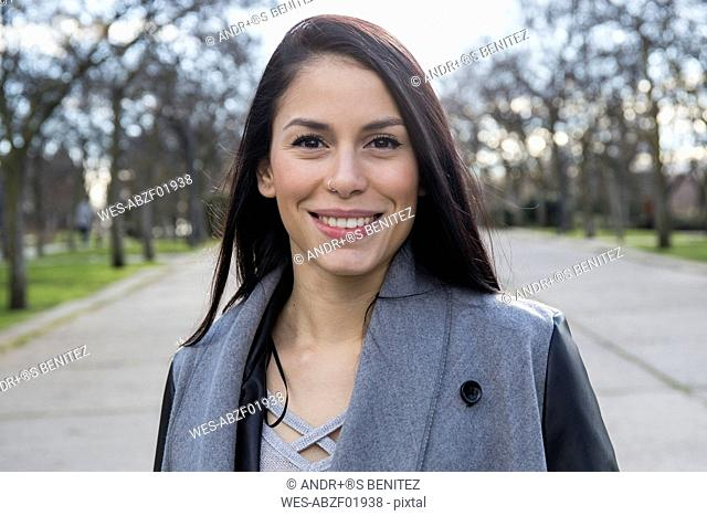 Portrait of smiling young woman with nose piercing in a park
