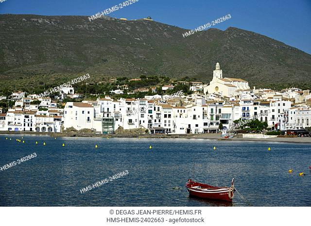 Spain, Catalonia, Costa Brava, province of Girona, Cadaques, wooden fishing boats in the middle of a bay with one city of white houses and a mountain in the...