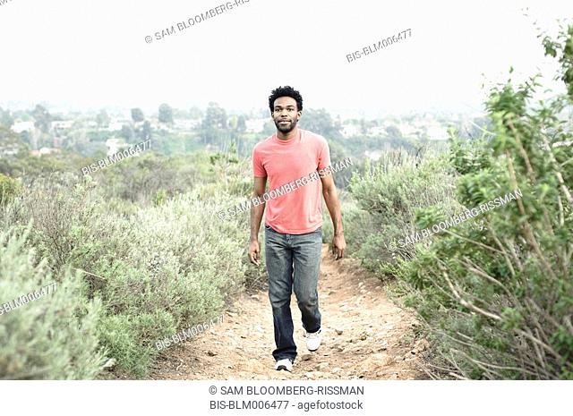 African American man walking on remote dirt path