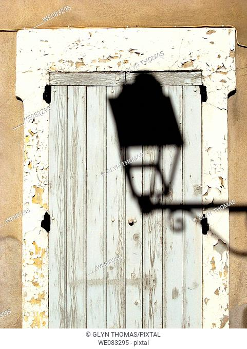 Shadow of an ornate lamp cast on an old door, Avignon, France
