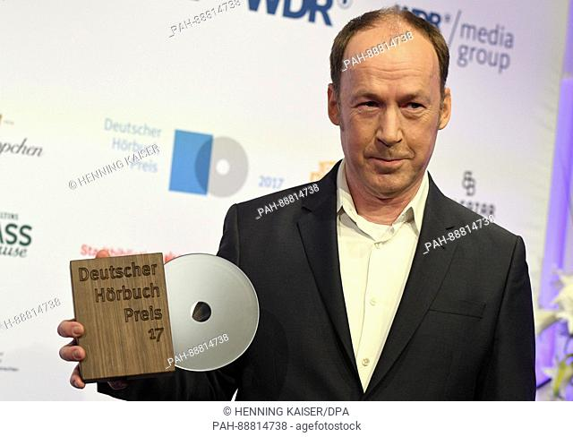 Actor Ulrich Noethen holds up his award in the category 'Best Male Interpreter' during a photocall before the ceremony of the German Audio Book Awards...