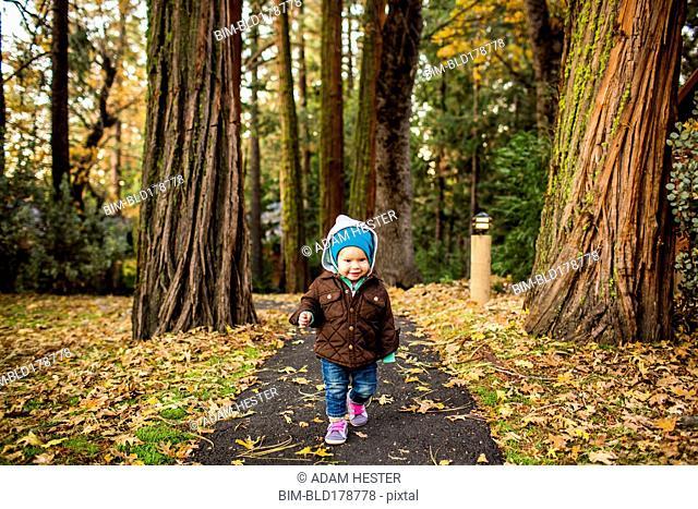 Caucasian baby girl walking in autumn park