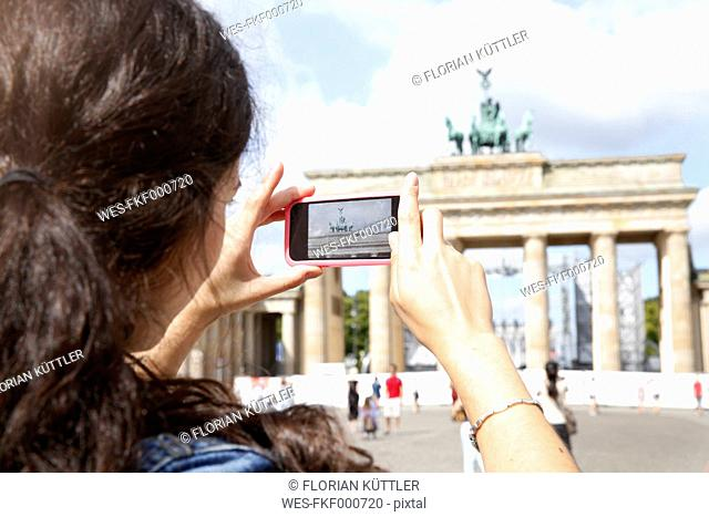 Germany, Berlin, female tourist photographing Brandenburg Gate with smartphone