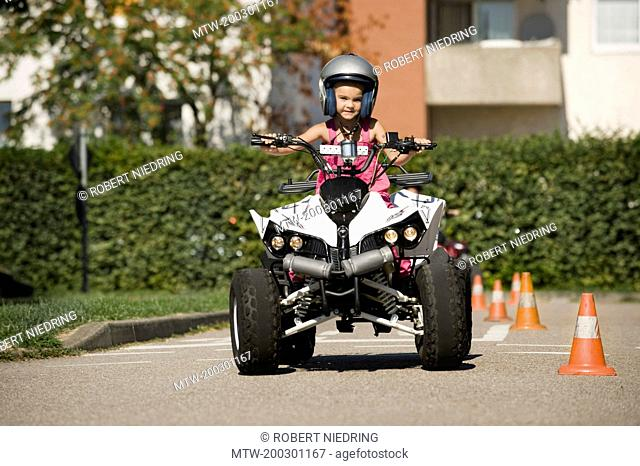 Girl with quadbike on driver training area
